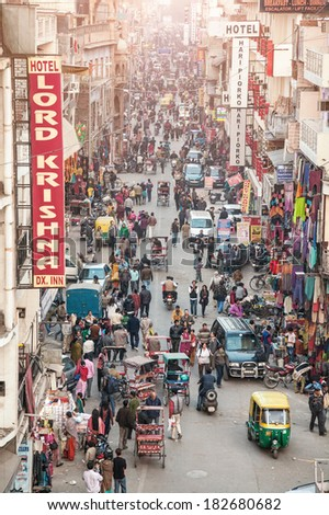 NEW DELHI, INDIA - JANUARY 29, 2012: View to crowded street with shops, hotels, transport and people in Main Bazaar or Paharganj. - stock photo