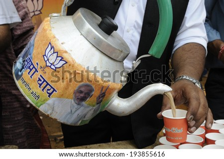 """NEW DELHI-MAY 16:  A BJP supporter pouring """"Namo chai"""" - to remember the fact that Modi was tea vendor ,while celebrating BJP's win of  Indian National election on May 16, 2014 in New Delhi , India.   - stock photo"""