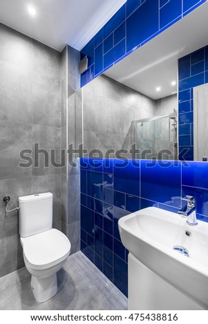 New design bathroom with mirror, sink, toilet, tiles in grey and blue