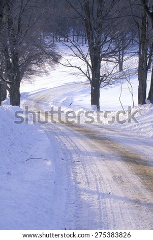 New England sunrise on a sunny and snowy road in Vermont - stock photo
