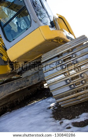 new excavator in the snow - stock photo