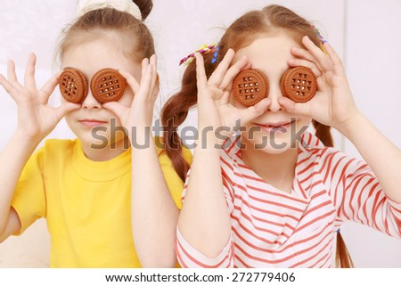 New eyes. Two funny little girls posing with cookies putting them to eyes - stock photo