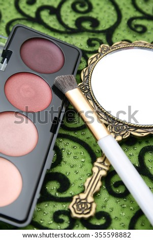 New eyeshadow set with used lipstick and small mirror. - stock photo