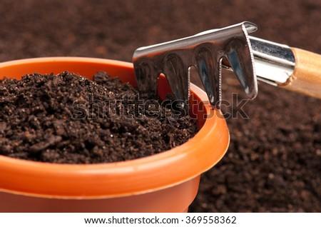 New garden rake over organic soil background - stock photo