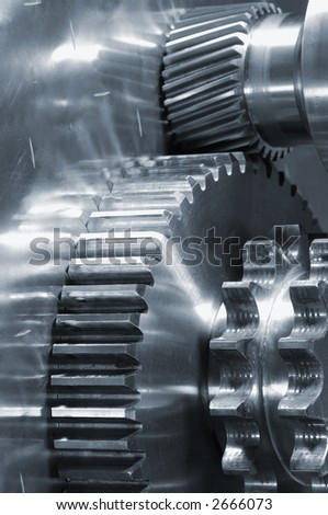 new gears and mechanical-parts against titanium in a blue tone - stock photo