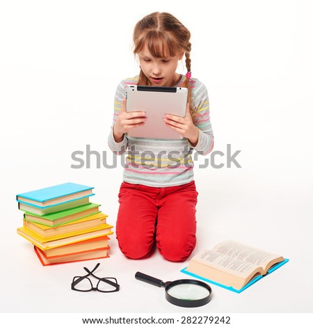 New generation. Little girl sitting on the floor with a lot of books, covering the face with a book reading, over white background - stock photo