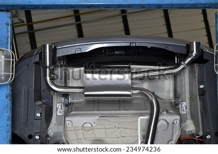 New generation of chromed exhaust pipe on powerful sport car bumper. - stock photo
