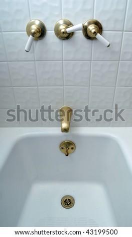 New golden bathtub valves on white tile - stock photo