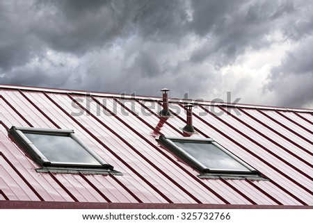 new grey metal roof with skylights against blue sky - stock photo