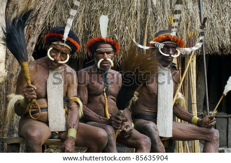 NEW GUINEA, INDONESIA -DECEMBER 28: Unidentified warriors of a Papuan tribe in traditional clothes and coloring in New Guinea Island, Indonesia on December 28, 2010 - stock photo