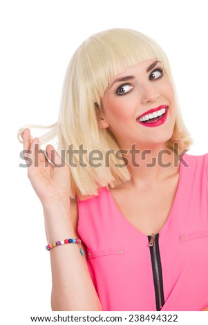 New hair color. Close up of smiling beautiful blonde young woman looking away and holding piece of hair. Waist up studio shot isolated on white. - stock photo