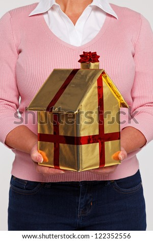 New home concept photo of a woman in casual clothing holding a house gift wrapped in gold paper with red ribbon and bow.