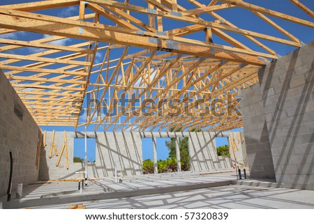 New home Construction of a cement block home with wooden roof trusses view from inside. - stock photo