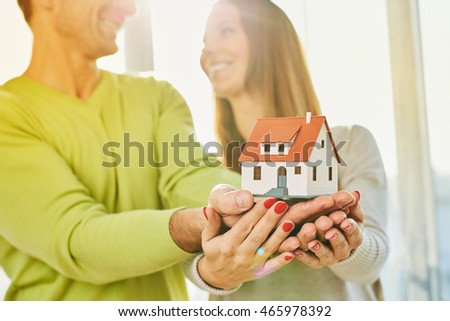 New home dreams concept - young couple holding small home figurine