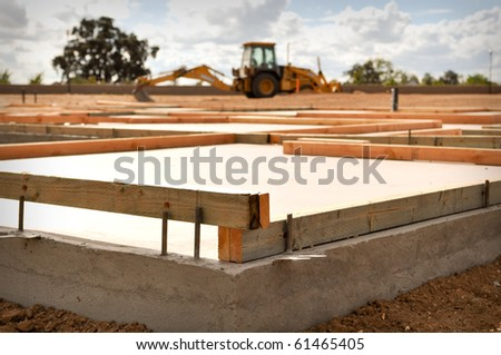 New Home Foundation with Tractor in Background - stock photo