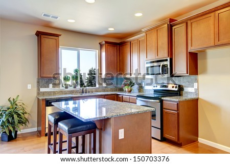 New home kitchen interior with dark brown cabinets and hardwood floors. - stock photo