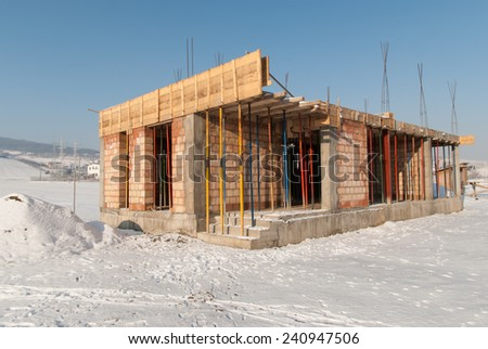 New house construction in winter. First floor of the new house is built but the construction is stopped due to bad weather conditions - stock photo