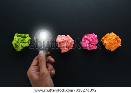 new idea concept with crumpled office paper, male hand holding light bulb - stock photo