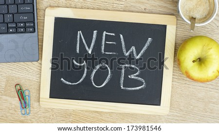 New job written on a chalkboarde at the office - stock photo