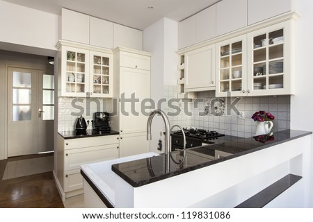New kitchen with bright furniture and flowers - stock photo