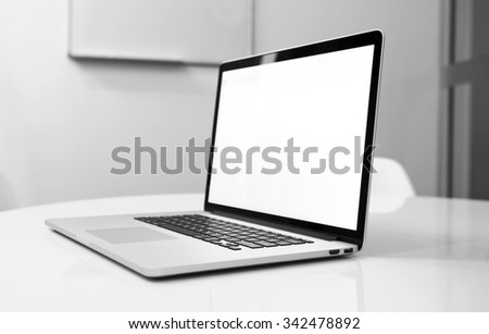 New laptop on table in black and white tones - stock photo
