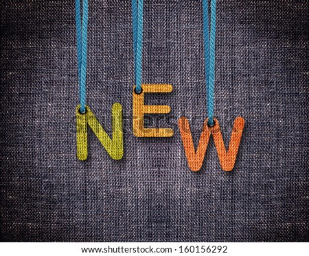 New letters hanging strings with blue sackcloth background. - stock photo