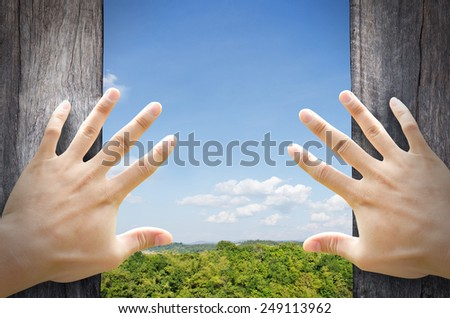 New life concept. 2 hands trying open a wooden door to new world. - stock photo