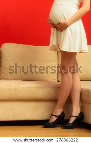 New life concept. Pregnancy, motherhood and elegance. tummy of pregnant woman wearing stylish white dress and long slim legs in high heels at home - stock photo