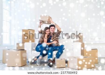 New life in a new home. Couple in love enjoys a new apartment and keep the box in his hands while young and beautiful couple in love sitting on the couch in an empty apartment among boxes. - stock photo