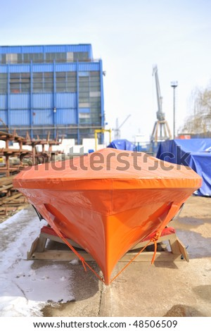 new lifeboat in shipyard storage place - stock photo