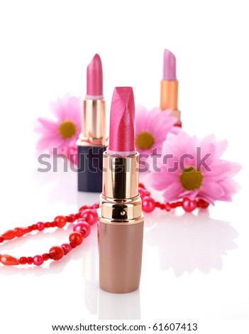 New lipstick on cosmetics and flower background - stock photo