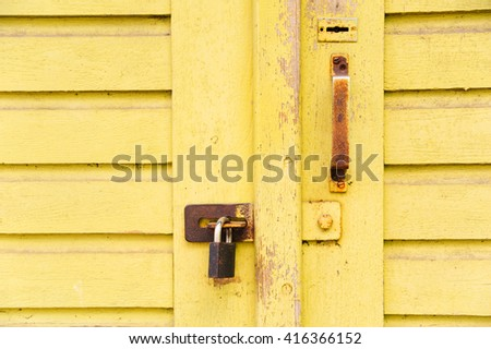 New lock on the old yellow cracked door with key hole - stock photo