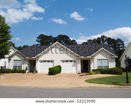 New low income small one story white vinyl duplex unit with garages in the front. - stock photo