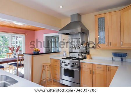 New Luxury modern fitted wooden kitchen with stainless steel appliances, white work surfaces, oven and dishwasher. - stock photo