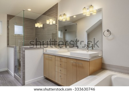 New master bathroom with lights on. - stock photo