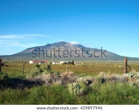 New Mexico, USA. Landscape on hot summer day. Green grass and pastures. Mountain in the background. Clear blue skies.