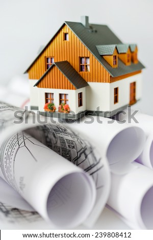new model house on architecture blueprint plan at desk - stock photo