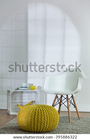 New modern design of living room with white armchair and yellow pouf - stock photo