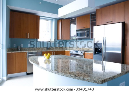 New modern kitchen interior with island in a condo apartment. Brightly lit, light blue walls, granite counter tops, stainless steel appliances. A bowl of lemons on the counter top. - stock photo