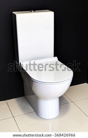 new modern white toilet bowl about a black wall - stock photo