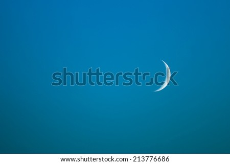 New Moon in the blue evening sky - stock photo