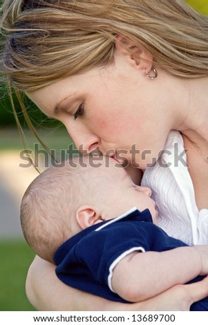 New Mother Kissing Baby's Forehead - stock photo