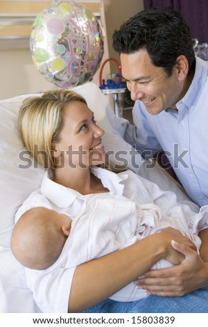 New mother with baby and husband in hospital smiling - stock photo