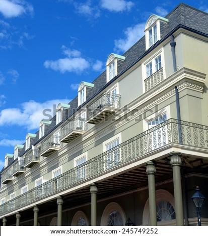 New Orleans French Quarter Architecture With Balcony Against Blue Sky With White Clouds - stock photo