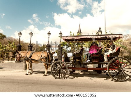 NEW ORLEANS - JANUARY 27, 2016: A horse and carriage awaits passengers in front of Jackson Square in the French Quarter. The city attracts 15 million tourists annually. - stock photo