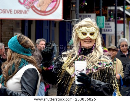 NEW ORLEANS, LA-FEBRUARY 17:  Masked revelers and party-goers parade through the streets of the New Orleans French Quarter in costumes on Mardi Gras Day, Tuesday, February 17, 2015.   - stock photo