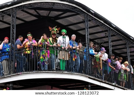 NEW ORLEANS, LA- FEBRUARY 12:  Tourist and locals alike celebrate Mardi Gras on February 12, 2013, from a New Orleans French Quarter Bourbon Street balcony. - stock photo