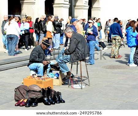 NEW ORLEANS, LA-JAN.31: A shoe shine man near Jackson Square in the New Orleans French Quarter polishes the shoes of a tourists in town for Mardi Gras on January 31, 2015. - stock photo