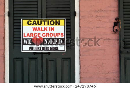 NEW ORLEANS, LA.-JANUARY 24:  A caution sign in the French Quarter warning tourists in town for Mardi Gras to walk in large groups, in New Orleans on January 24, 2015, due to a  recent crime spree. - stock photo