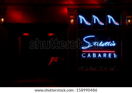 NEW ORLEANS, LA - 6 OCTOBER 2013: Neon Sign and Woman's Legs at Entry to Strip Club on Bourbon Street in New Orleans on 6 October 2013. - stock photo